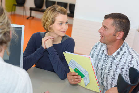 couple talking with salesman and singing contract in the office Stock Photo