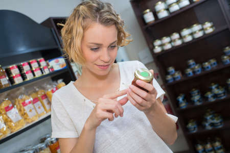 preocupacion: woman reading ingredients of a product in shop