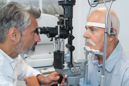 old man having her eyes examined by eye doctor