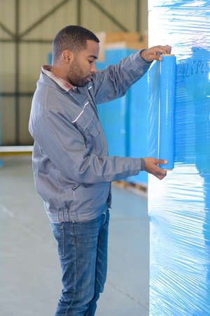 overseer: worker wrapping merchandise with plastic Stock Photo