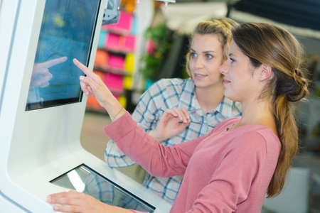 touch screen: shop assistant helping customer to use touch screen