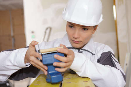 female builder preparing sanding machine Stock Photo