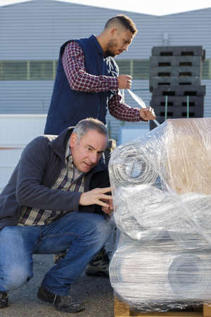 isolators: laborers outside a factory unwrapping shipping