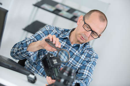 ged: middlea ged man examining dslr camera with mgnifying glass Stock Photo