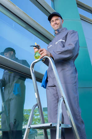 man cleaning windows with squeegee Banco de Imagens