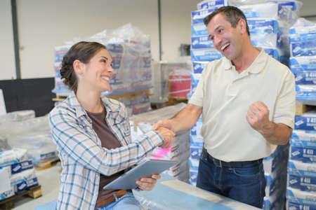 warehouseman: female worker shake hand with male worker in warehouse