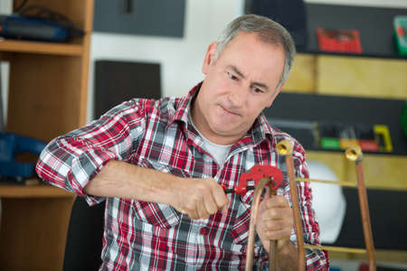 male plumber using clamp Stock Photo