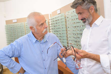 handsome optician showing glasses to senior man at optics store