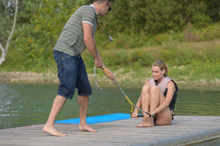 coach explaining woman how to do wakeboard