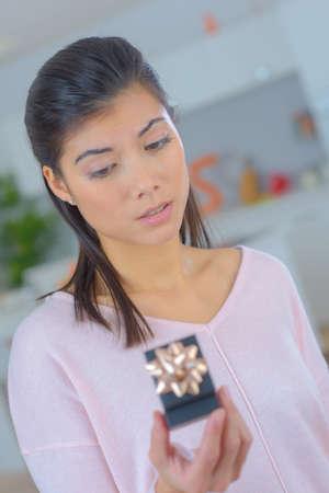 beautiful eurasian woman looking at enagement ring and doubting