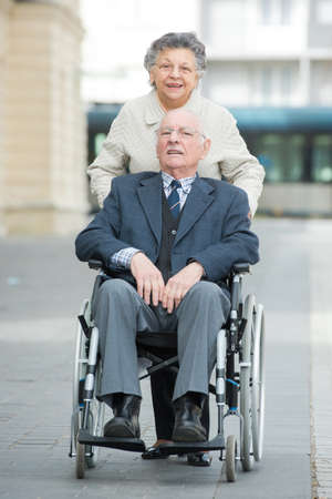 seventy: senior lady pushing her husband in his wheelchair Stock Photo