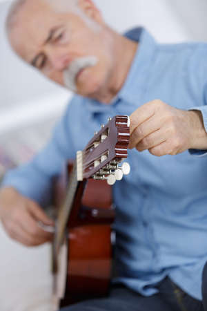 retired man tuning classical guitar