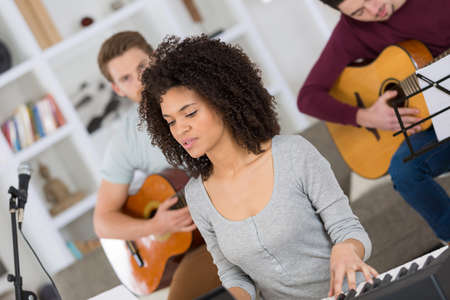 multiracial music band rehearsing in the living room Stock Photo