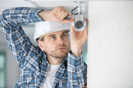 wirework: portrait of a male electrician fixing light on ceiling Stock Photo