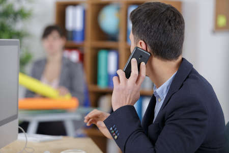 serious businessman is talking on mobile phone with managing director Stock Photo