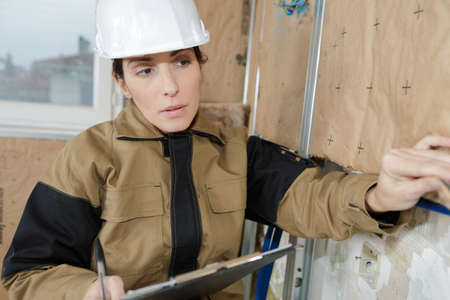 woman is insulating the wall with boards Stock Photo