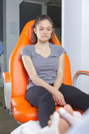 female getting foot massage at massage center