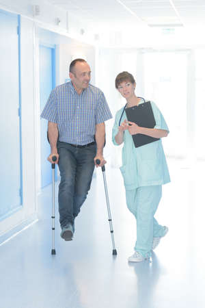 nurse helping man with crutches in hospital corridor