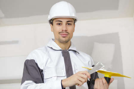 concrete surface finishing: builder with spatula with plaster in hand Stock Photo