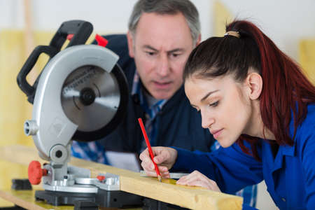 young woman working at carpenter shop with her teacher Stock Photo