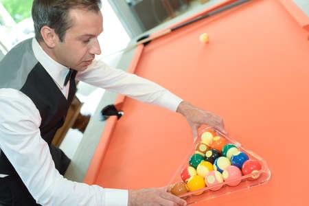 pool player placing billiard balls in triangle