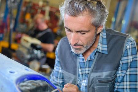 portrait of mature diligent mechanic man working with bike Stock Photo