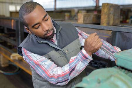designate: skilled young african craftsman working in workshop