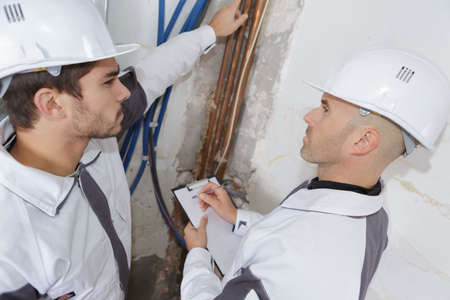 professional occupation: plumbers checking cooper pipes