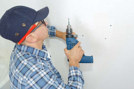 man ready to drill the wall with perforator