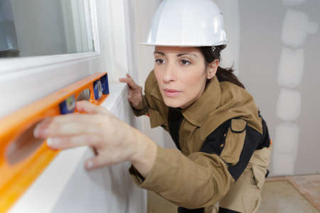 plasterer: construction female worker using a level tool on house wall