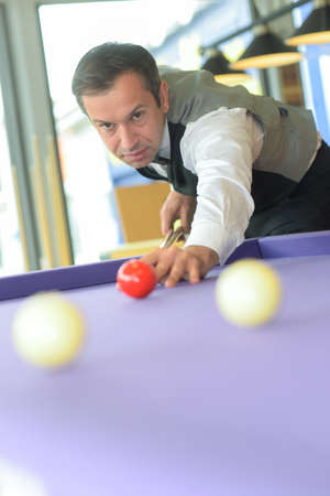confident young man playing pool and looking concentrated