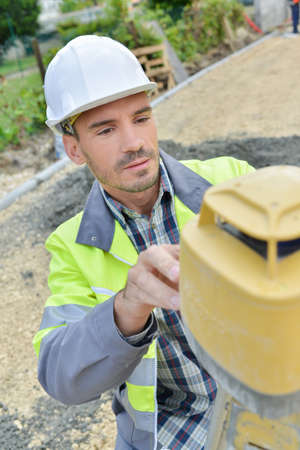 tacheometer: male construction builder taking measurements at construction site