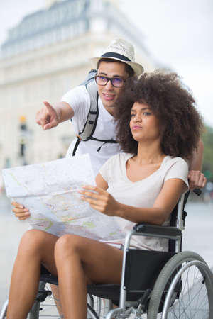 scenic spots: young couple visiting city - female on wheelchair Stock Photo