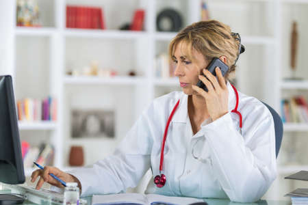 female doctor at her desk talking on phone Stock Photo