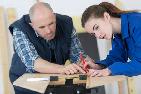 carpenter with female apprentice in training period
