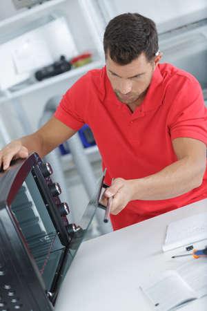부엌에 오븐을 설치하는 남자