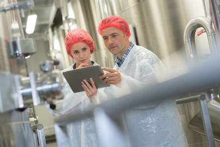 man pointing at something to his colleague in the factory Stock Photo