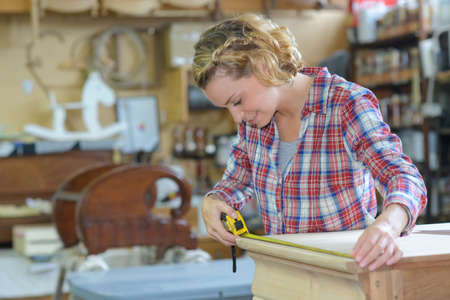 female worker measuring a wood table Stock Photo