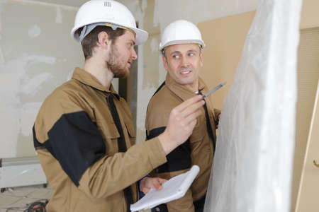 builders installing thermal insulation for walls