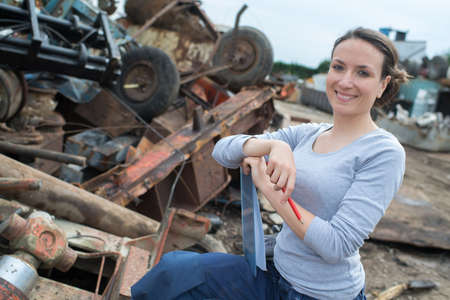 woman working next to a rusted metal scrap pile