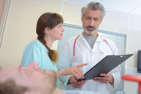 metro de medir: Octor y enfermera con el paciente en el hospital