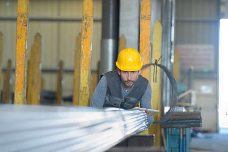 worker moving steel bar storing inside warehouse