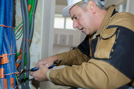 plumber cutting some pipes indoors construction Stock Photo