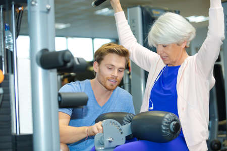 securing: personal trainer securing gym equipment around senior woman