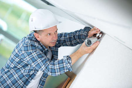 mature male technician fitting cctv camera on wall