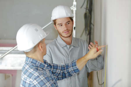site inspector talking with construction workers Stock Photo