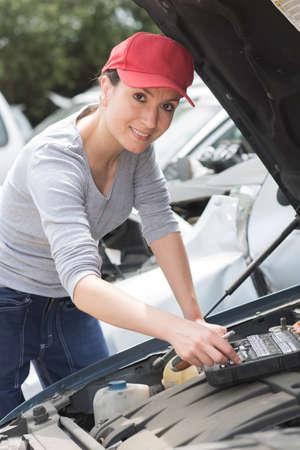 mechanician: woman car mechanician repairs engine of car and smiles