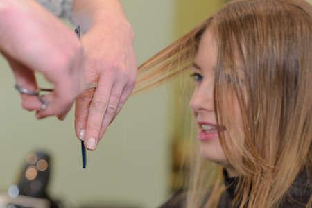 haircutting: hairdresser cut hair of a woman Stock Photo