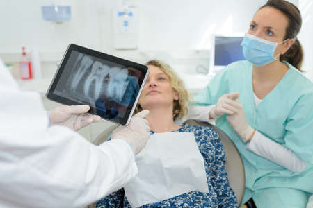 dentist showing xray to her female colleague and patient