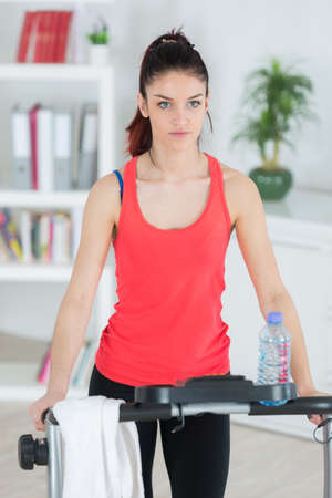 young attractive girl exercise at home on step machine Stock Photo